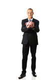 Happy businessman holding piggybank. Smiling mature businessman holding piggybank Stock Photos