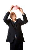 Happy businessman holding piggybank. Smiling mature businessman holding piggybank Stock Photo