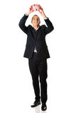 Happy businessman holding piggybank. Smiling mature businessman holding piggybank Stock Images