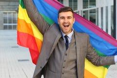 Happy businessman holding the rainbow flag.  stock photo