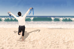 Happy businessman holding snorkeling gear. Backside of happy businessman holding snorkeling gear at beach Royalty Free Stock Images