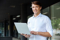Happy businessman holding and using laptop Stock Image