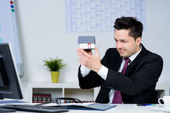 Happy businessman with a house model. In the office royalty free stock image