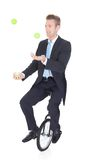 Happy Businessman Juggling. Ball Sitting On Unicycle Royalty Free Stock Photo