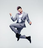 Happy businessman jumping in air. Over gray background Royalty Free Stock Photo
