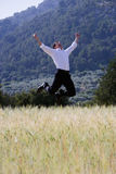 Happy businessman jumping with arms outstretched in rural field Stock Photography