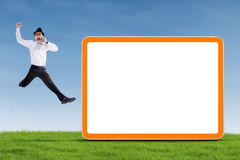 Happy businessman jumping with blank board Stock Images