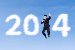 Happy businessman jumping with clouds of 2014. On the blue sky Royalty Free Stock Images