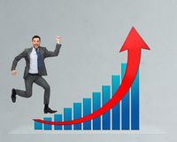 Happy businessman jumping over growth chart Royalty Free Stock Photography