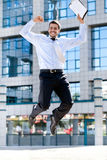 Happy businessman jumps in the air. Jumping happy businessman over office buildings Stock Image