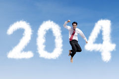 Happy businessman jumps with clouds of 2014 Royalty Free Stock Image
