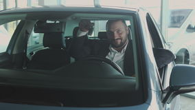 Happy businessman with keys inside his new car in car dealership stock video footage