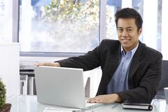 Happy businessman with laptop Stock Images