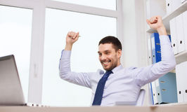 Happy businessman with laptop cheering in office Royalty Free Stock Images