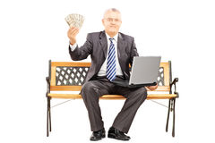 Happy businessman with laptop sitting on bench and holding money Royalty Free Stock Images