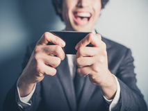 Happy businessman laughing at his smartphone Royalty Free Stock Photo