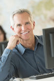Happy Businessman Leaning At Computer Desk Royalty Free Stock Photography