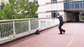 Businessman dancing. Happy businessman leaving the office wearing headphones and dancing