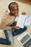 Happy businessman listening to music. Hobby. Good-looking inspired afro-american man listening to music while working on the laptop and sitting on the floor and Stock Photo