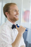 Happy businessman looking away while holding felt tip pen at creative office Royalty Free Stock Photo