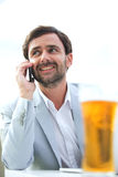 Happy businessman looking away while using mobile phone at outdoor restaurant Royalty Free Stock Images