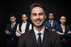 Happy businessman looking at camera with group of coworkers behind Royalty Free Stock Image