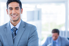 Happy businessman looking at camera with his colleagues behind Stock Images