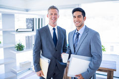 Happy businessman looking at camera and holding files Royalty Free Stock Photography
