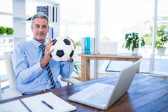 Happy businessman looking at camera and holding foot ball Royalty Free Stock Image