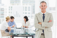 Happy businessman looking at camera while staff discuss behind him Stock Images