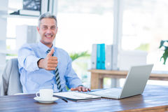 Happy businessman looking at camera with thumbs up Royalty Free Stock Image