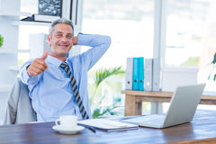 Happy businessman looking at camera with thumbs up Stock Photos