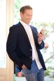 Happy businessman looking at mobile phone Royalty Free Stock Photos