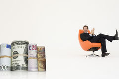 Happy businessman looking at money rolls representing growth in international business Royalty Free Stock Photo