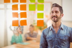Happy businessman looking post its on the wall Stock Images