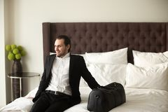 Happy businessman with luggage sitting on bed in hotel room. stock image
