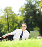 Happy businessman lying on a grass and working on a laptop in pa Royalty Free Stock Image