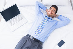 Happy businessman lying on his bed Stock Images