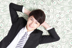 Happy businessman lying on money bed Royalty Free Stock Photos
