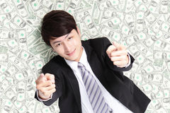 Happy businessman lying on money bed Royalty Free Stock Photography