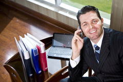 Happy businessman on mobile phone in office Stock Photography