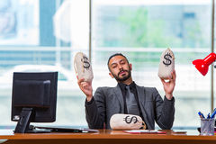 The happy businessman with money sacks in the office Royalty Free Stock Image