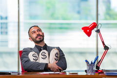 The happy businessman with money sacks in the office Stock Image