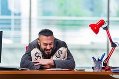 The happy businessman with money sacks in the office Stock Images