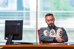 The happy businessman with money sacks in the office Royalty Free Stock Photo