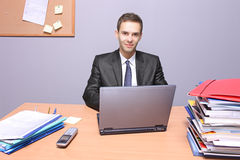 Happy businessman in the office. A view of a happy businessman in the office royalty free stock photos