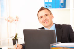 Happy businessman in office Royalty Free Stock Image