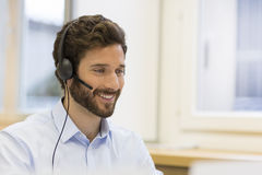 Happy Businessman in the office on the phone, headset, Skype. Man talking on skype at the office Stock Image