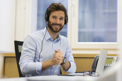 Happy Businessman in the office on the phone, headset, Skype. Man in teleconference on his laptop at this office Royalty Free Stock Photo