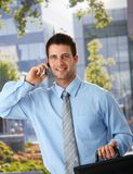 Happy businessman outside of office on phone Royalty Free Stock Image
